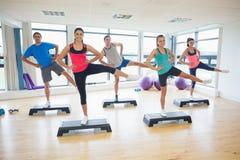 Instrutor com a classe da aptidão que executa o exercício da ginástica aeróbica da etapa Fotos de Stock Royalty Free