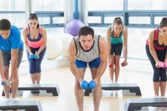 Instrutor com a classe da aptidão que executa o exercício da ginástica aeróbica da etapa com os pesos Fotos de Stock