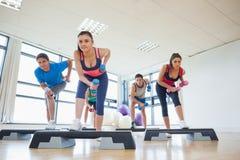 Instrutor com a classe da aptidão que executa o exercício da ginástica aeróbica da etapa com os pesos Imagens de Stock