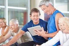 Instrutor da aptidão com o tablet pc no gym Fotos de Stock