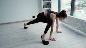 Instrutor da aptidão da menina que estica seus pés no assoalho do gym usando o disco de deslizamento vídeos de arquivo