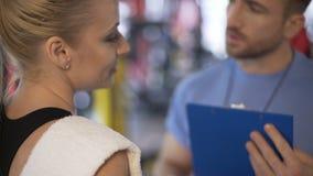 Instrutor da aptidão que comunica-se com o cliente fêmea no gym, trabalhando em seu programa video estoque