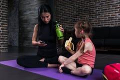 Instrutor da criança da ioga e uma menina que tem uma ruptura após o exercício que senta-se na esteira que come o petisco, água p imagem de stock