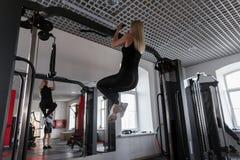 Instrutor da jovem mulher no sportswear com um corpo magro que faz exercícios para as mãos dentro A menina executa o esforço físi fotos de stock royalty free