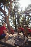 Instrutor e crianças que levam logs de madeira durante o treinamento do curso de obstáculo foto de stock royalty free