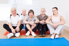 Instrutor fêmea com os clientes superiores no gym Foto de Stock Royalty Free