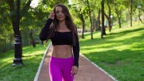 Instrutor fêmea de sorriso no passeio superior do esporte curto no parque após o treinamento intensivo Mulher saudável apta do es video estoque