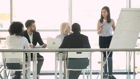Instrutor fêmea que fala na reunião do escritório que dá a apresentação do negócio vídeos de arquivo