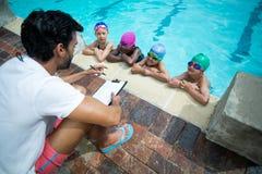 Instrutor masculino com os nadadores pequenos de explicação da prancheta no pooldise Fotos de Stock
