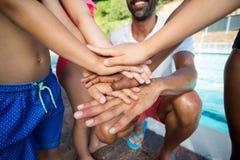 Instrutor masculino e crianças que empilham as mãos na piscina foto de stock