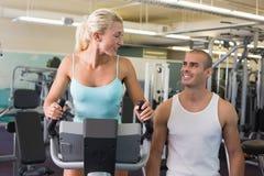 Instrutor masculino que ajuda à mulher com a bicicleta de exercício no gym foto de stock royalty free
