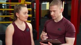 Instrutor muscular e jovem mulher pessoais que discutem um plano de formação no gym vídeos de arquivo