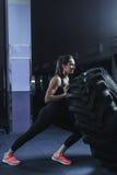 Instrutor muscular poderoso de CrossFit da mulher que faz o exercício do pneu no gym Fotos de Stock Royalty Free