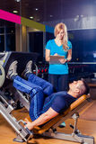 Instrutor pessoal ajudando os homens que dão certo na máquina da imprensa do pé no gym imagem de stock