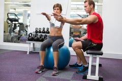 Instrutor pessoal com o cliente que senta diretamente a bola do exercício foto de stock