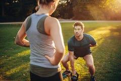 Instrutor pessoal com o homem que faz o treinamento do peso no parque foto de stock royalty free