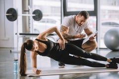 Instrutor pessoal masculino que olha o temporizador e a mulher atlética nova imagem de stock royalty free