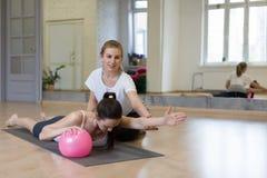 Instrutor pessoal, pilates Dois trabalhos das mulheres com a bola apta pequena, uma ajudam outra a fazer o exersice para sua part foto de stock