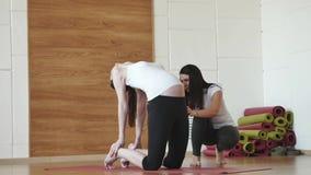 Instrutor pessoal que ajuda à mulher gravida ao fazer a ioga filme