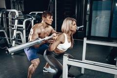 Instrutor pessoal que ajuda uma jovem mulher a levantar um barbell ao dar certo em um gym imagens de stock