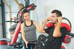 Instrutor pessoal que instrui o estagiário no gym imagem de stock royalty free