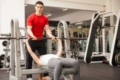 Instrutor pessoal que mancha uma mulher no gym fotos de stock royalty free