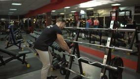 Instrutor pessoal que prepara o local para seus clientes no gym, profissão do treinamento video estoque