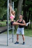 Instrutor pessoal segurando a mulher durante o exercício Fotos de Stock Royalty Free