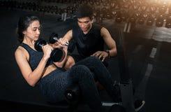 Instrutor que exercita com seu cliente no gym, mulher de ajuda da aptidão do instrutor pessoal que trabalha com pesos pesados foto de stock