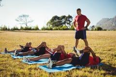 Instrutor que instrui crianças ao exercitar no campo de treinos de novos recrutas fotos de stock royalty free