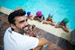 Instrutor que usa o cronômetro com os nadadores pequenos na piscina Fotografia de Stock