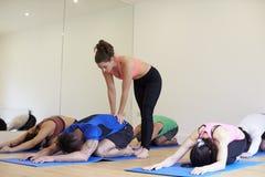Instrutor With Yoga Class no Gym imagem de stock