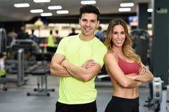 Instrutores pessoais do homem e da mulher no gym imagens de stock