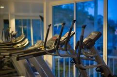 Instrutores transversais elípticos em um gym da aptidão na noite Fotos de Stock