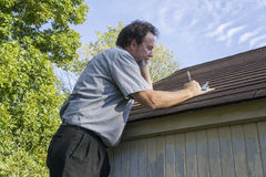 Insuance Adjuster On Cell Phone Calculating Roof Repair Costs Stock Photos