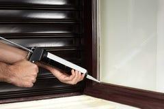 Insulate with caulking gun tool stock photo