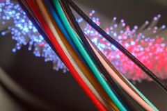 Insulated cables with different colors with fiber optic wires glowing pink and lilac stock photo