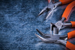 Insulated electric nippers gripping tongs on scratched metallic Royalty Free Stock Images