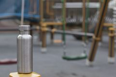 Insulated Stainless Bottle with a children´s playground in winter background royalty free stock photo