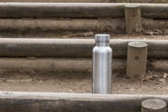 Insulated Stainless Bottle on log steps in the forest stock photo