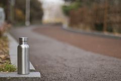 Insulated Stainless Bottle on the paved trail in the forest stock photography