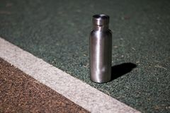 An insulated stainless steel bottle at the track in the night stock photo