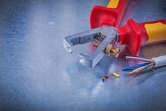 Insulated strippers electrical wires on scratched metallic backg Royalty Free Stock Photos
