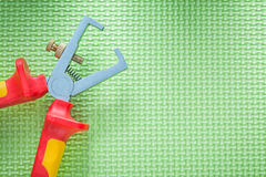 Insulated wire strippers on green surface electricity concept Royalty Free Stock Image