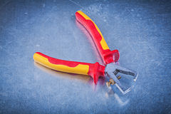 Insulated wire strippers on scratched metallic background electr Stock Photos
