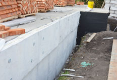 Insulating Exterior Foundation Walls. Foundation Waterproofing and Damp proofing Coatings. Waterproofing house foundation. With spray on tar with insulation Royalty Free Stock Photography
