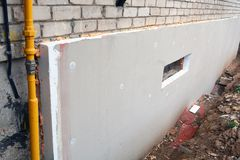 Insulating old flat house foundation with white polystyrene Royalty Free Stock Photo