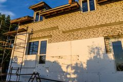 Insulation of the house with styrofoam. Scaffold on building. Insulation of house with styrofoam. Scaffold on building stock image
