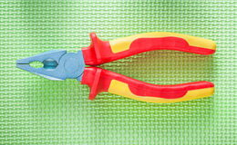 Insulation pliers on green surface electricity concept Stock Photography