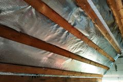 Insulation of the roof of the house on the inside with the use of a wrapper film and fixing boards stock photography